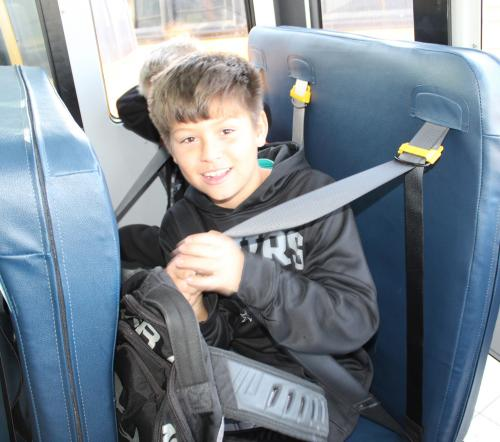 boy puts on school bus seatbelt