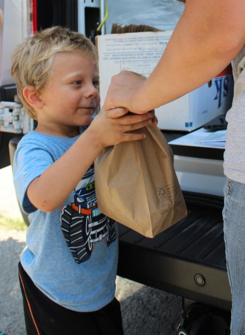 Local boy accepts sack lunch at meal site