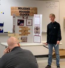 boys presents clock project to judges