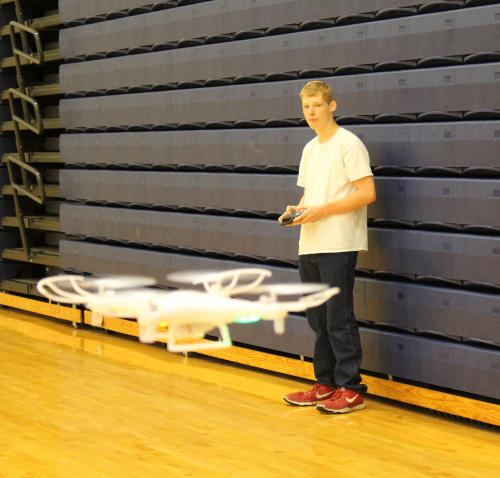 CHS junior practices flying a drone in the school gymnasium