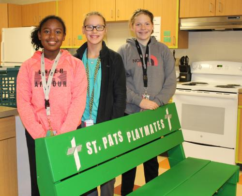 RMS girls stand behind buddy bench