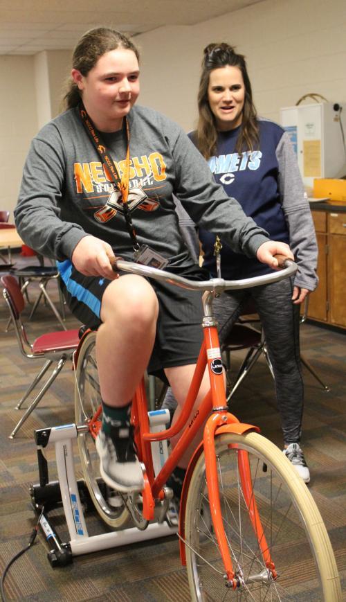 girl pedals bike generator in class