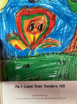 Music teacher shows book created with CES student artwork