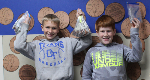 boys hold up collection bags of coins