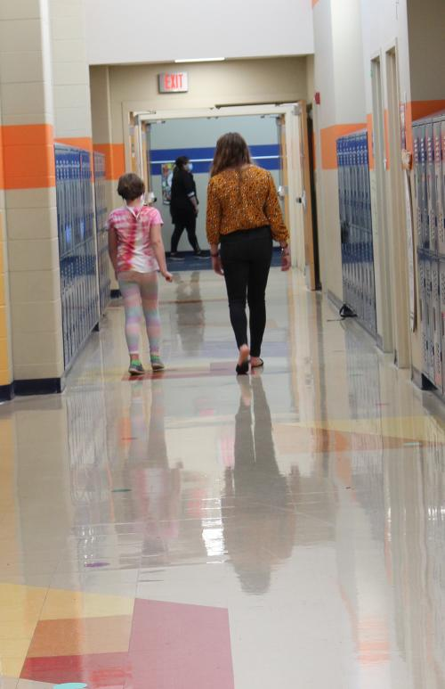 liaison walks down hallway with student