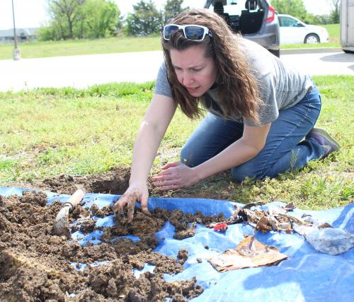 teacher digs through remains of buried pumpkin