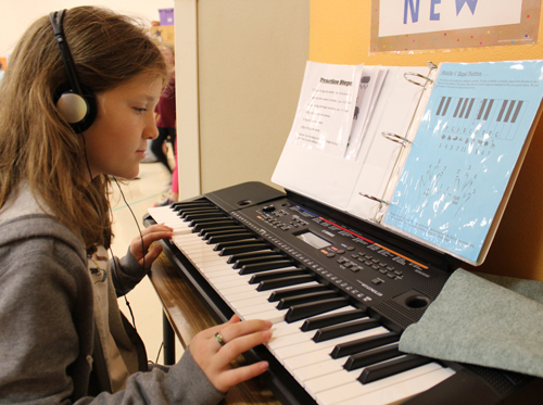 student practices playing keyboard before school