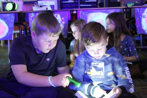 reading by flashlight under the stars in third grade classroom