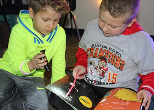 boys read by flashlight in wolf's classroom