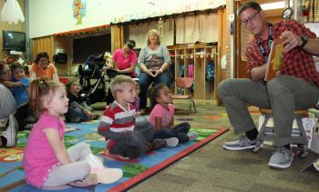 Mr. Applegate reads to the preschool kids
