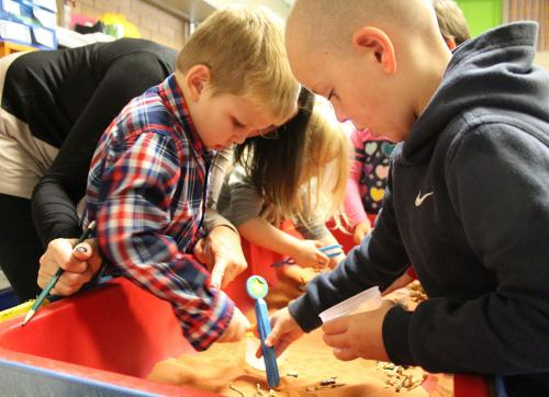 boys dig for treasure in sandbox