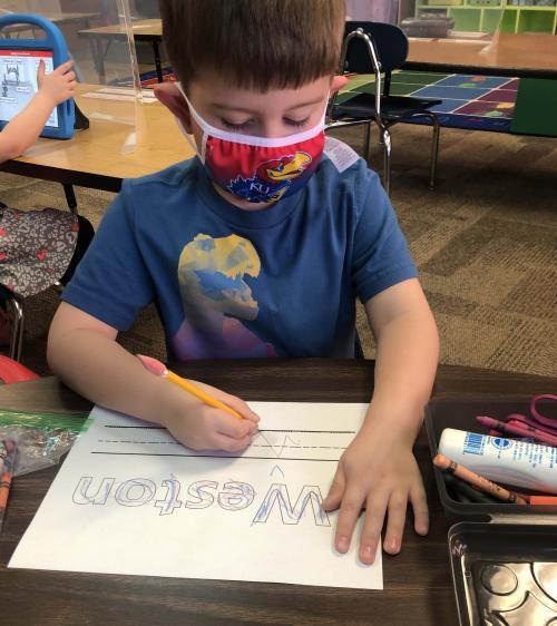 boy writes his name