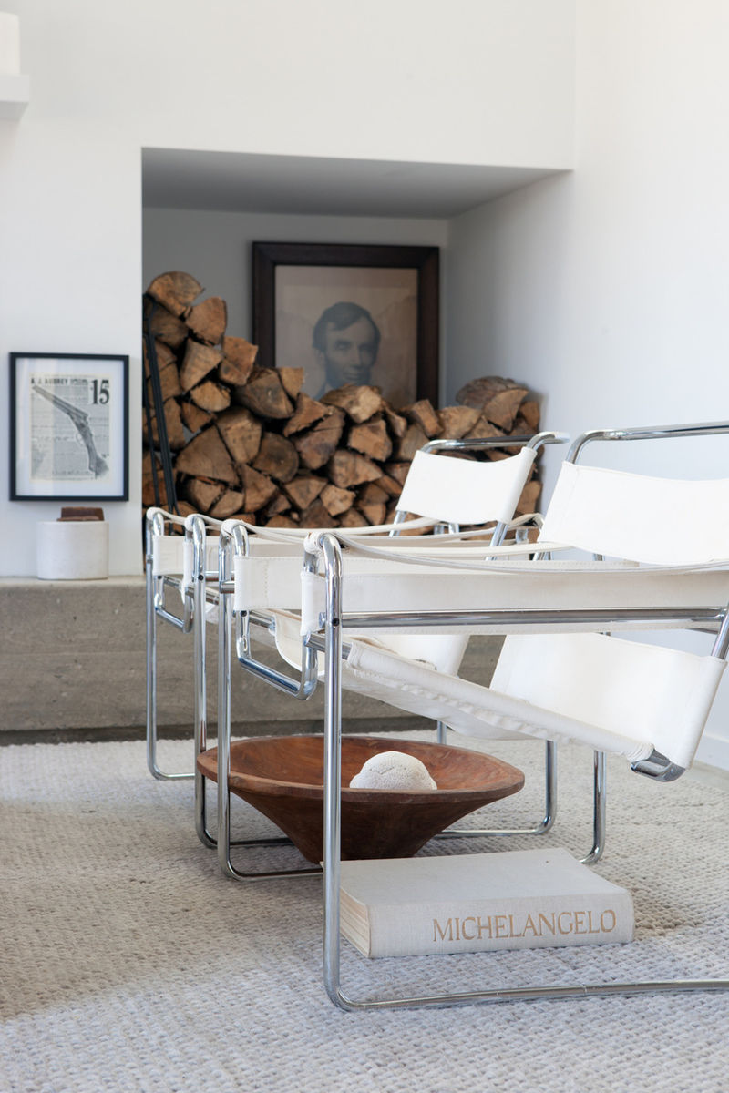 White leather Midcentury Modern Wassily Breuer chairs in a rustic modern chic room designed by Leanne Ford with firewood, vintage treasures, and an all white design scheme. #leanneford #wassily #midcentury #rusticdecor #rusticchic #allwhite