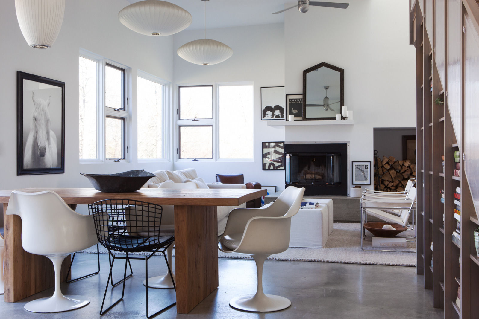 All white and modern design pairs with rustic chic in this living space and dining area by Leanne Ford. A live edge rustic wood table mingles with Midcentury style chairs on a polished concrete floor. #midcentury #rusticdecor #allwhite #bohochic #leanneford