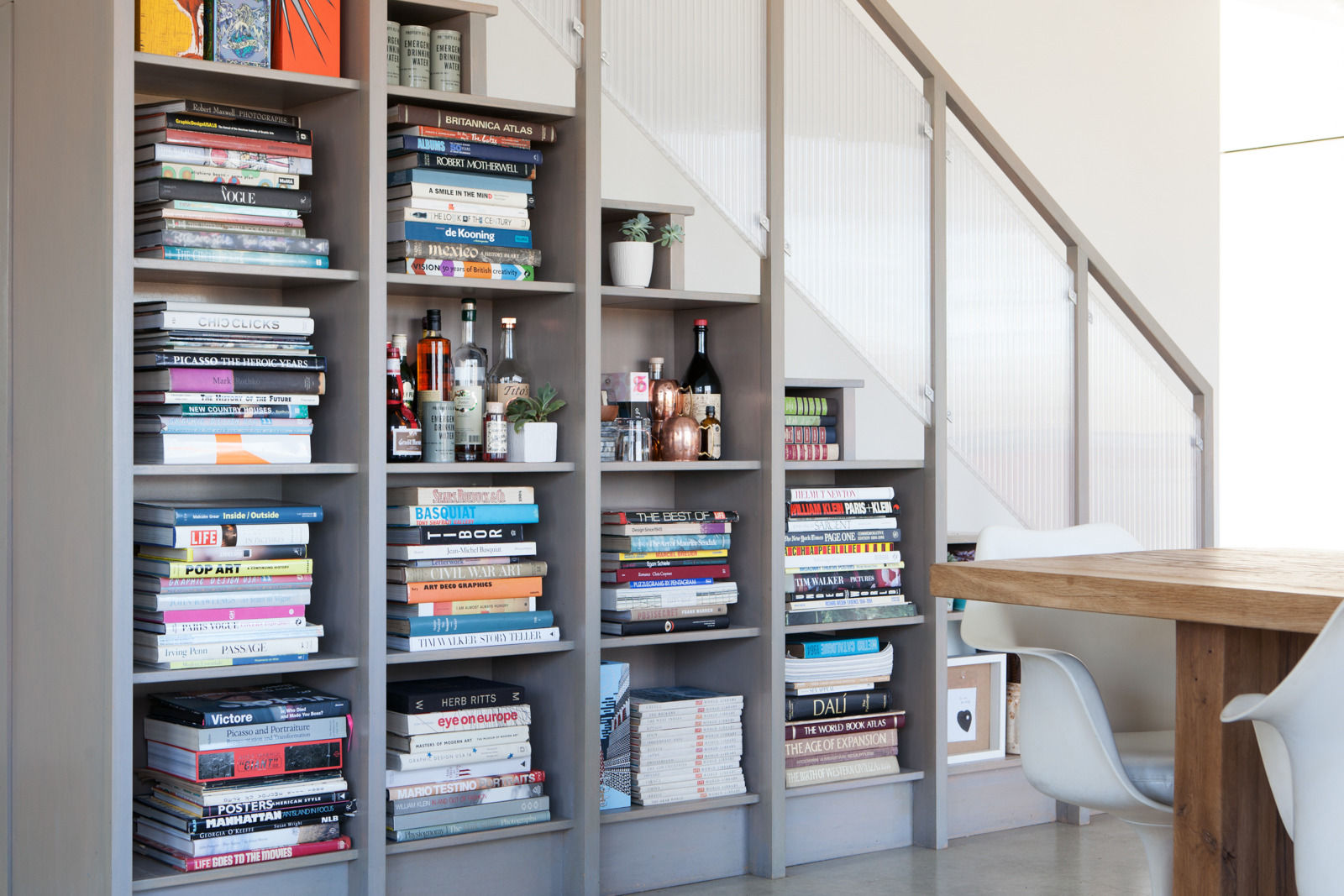 Built-in book shelves under a stairway provide smart display and storage space for books, booze, and bits in a space designed by Leanne Ford. #midcentury #boho #edgy #rusticdecor