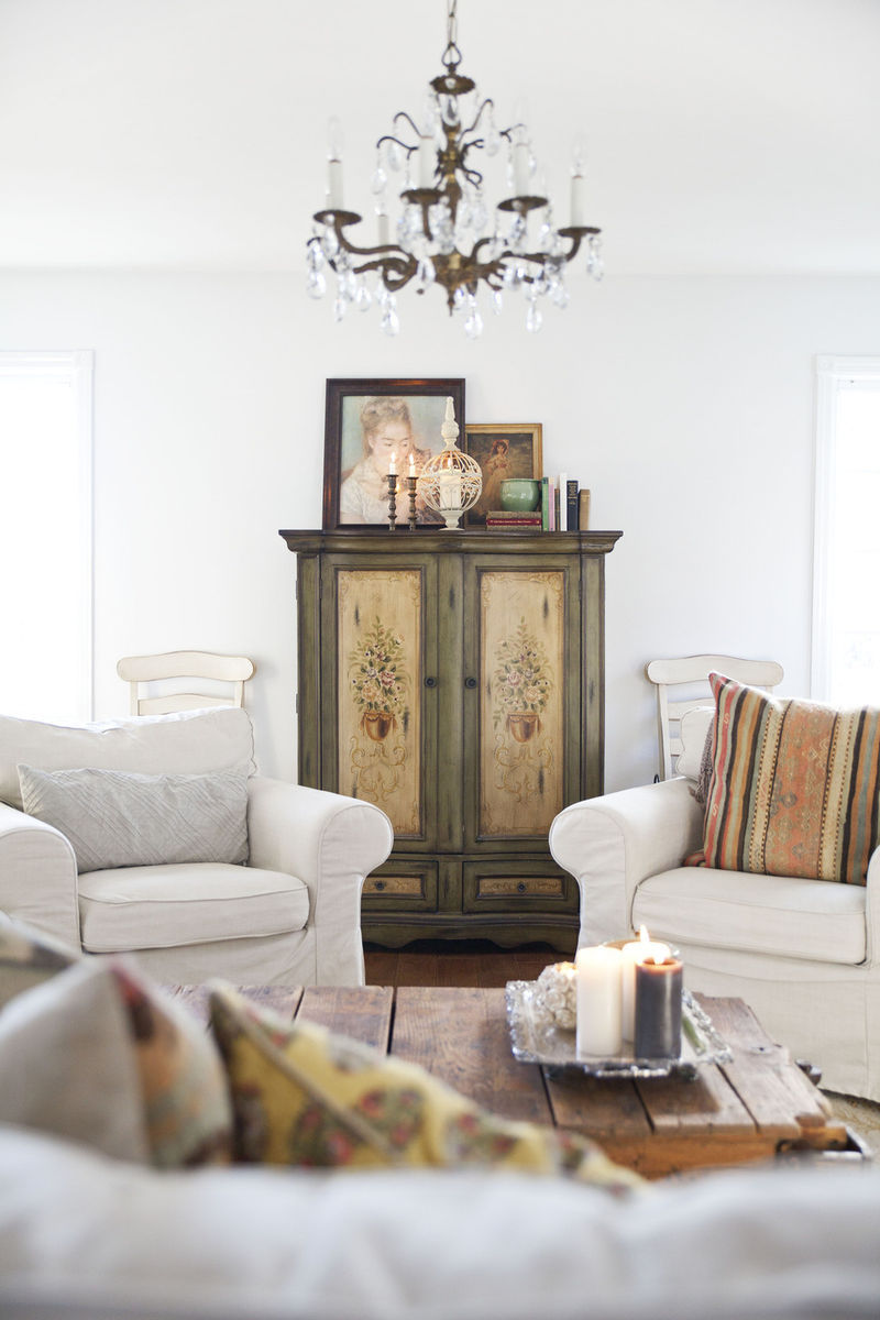 Leanne Ford living room with beachy white club chairs (maybe Ektorps from Ikea?), an antique brass crystal chandelier, painted vintage cabinet, and edgy cool vintage flea market treasures. #leanneford #shabbychic #allwhite #rusticdecor #bohochic