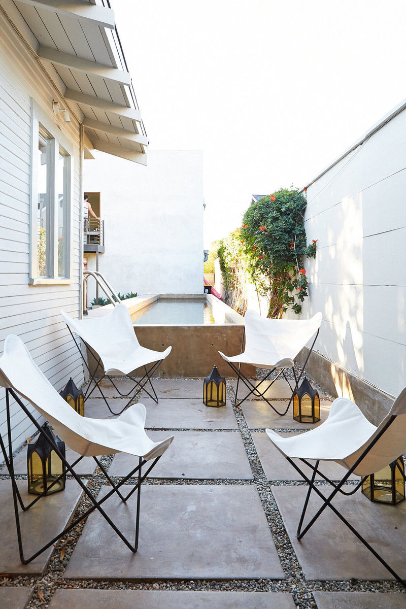 Creamy butterfly chairs on a cement and gravel patio designed by Leanne Ford. California chic and edgy retro outdoor decor! #patio #butterflychair #minimal