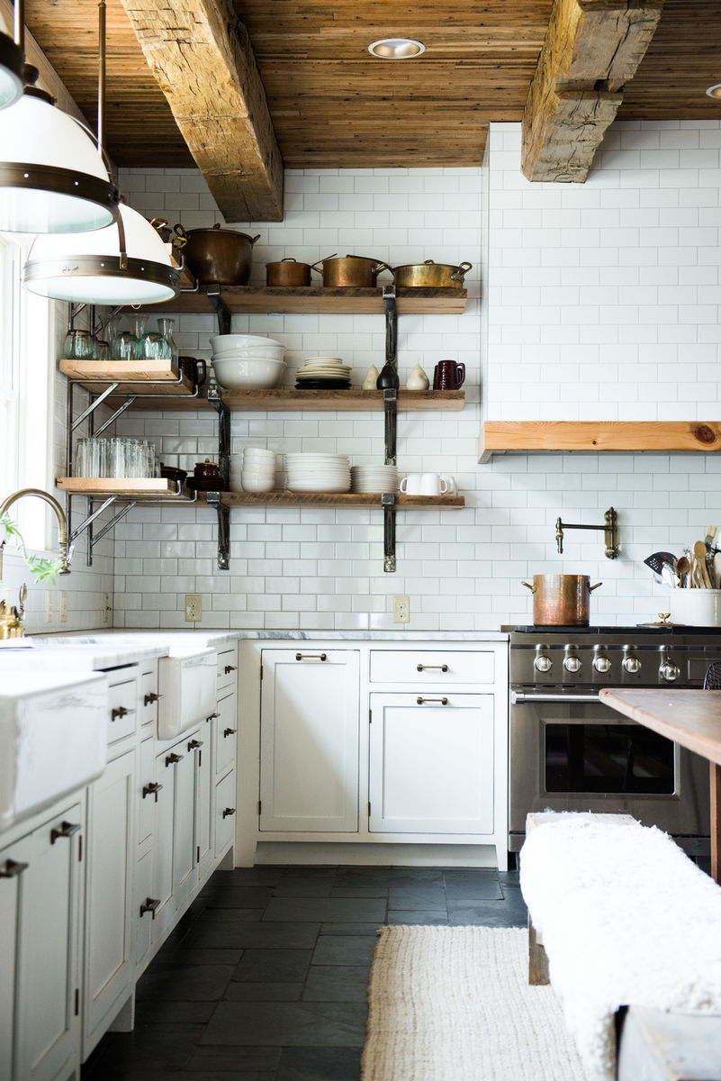 Leanne Ford Interior Design Ideas - a white kitchen with two farm sinks! Open shelving, rustic wood ceiling, dark flooring, and big farm table create a modern farmhouse style kitchen to love! #modernfarmhouse #kitchendesign #interiordesignideas #farmhousekitchen #leanneford #rusticdecor #whitekitchen #rusticmodern #farmhousedecor