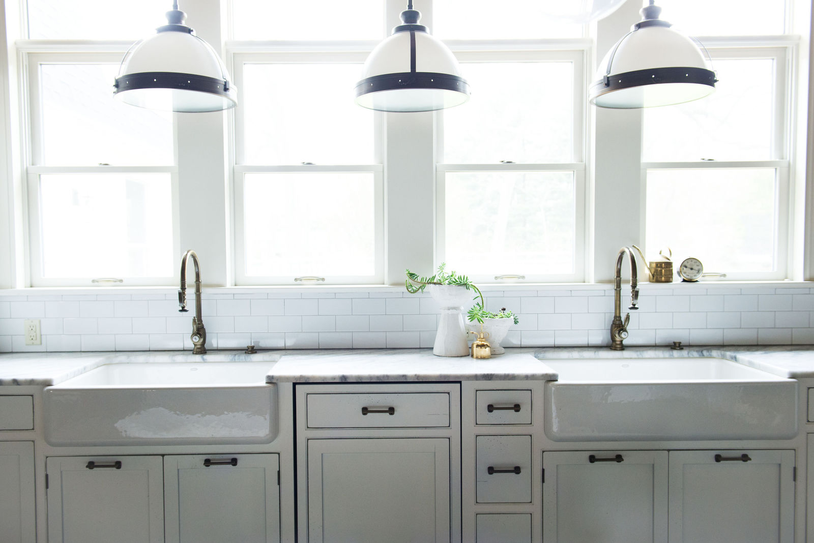 White kitchen with two farm sinks, subway tile, and large pendant lights. Leanne Ford.