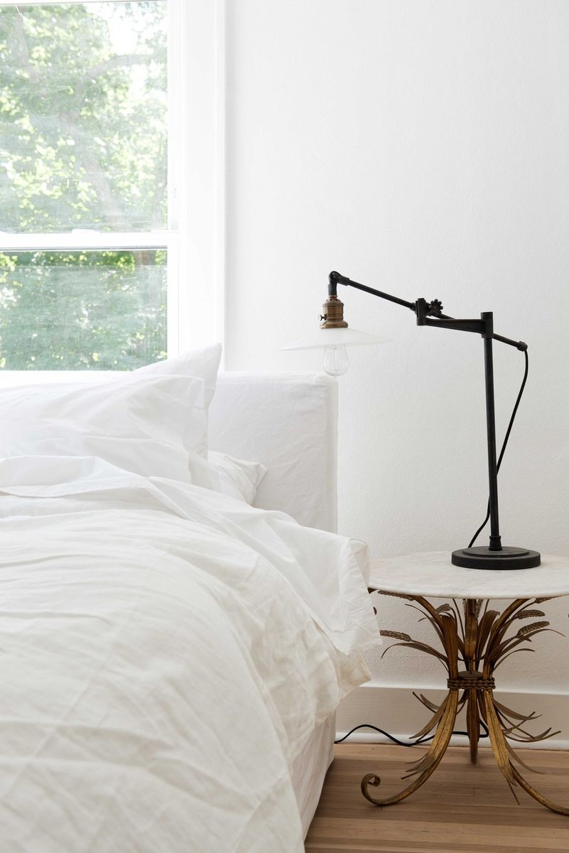 White bedroom with interior design by Leanne Ford and bohemian decor. Midcentury modern side table and industrial style lamp with white walls and bedding. #whitebedroom #bedroomdecor #bohemian #blackandwhite #leanneford #restoredbythefords #vintagestyle