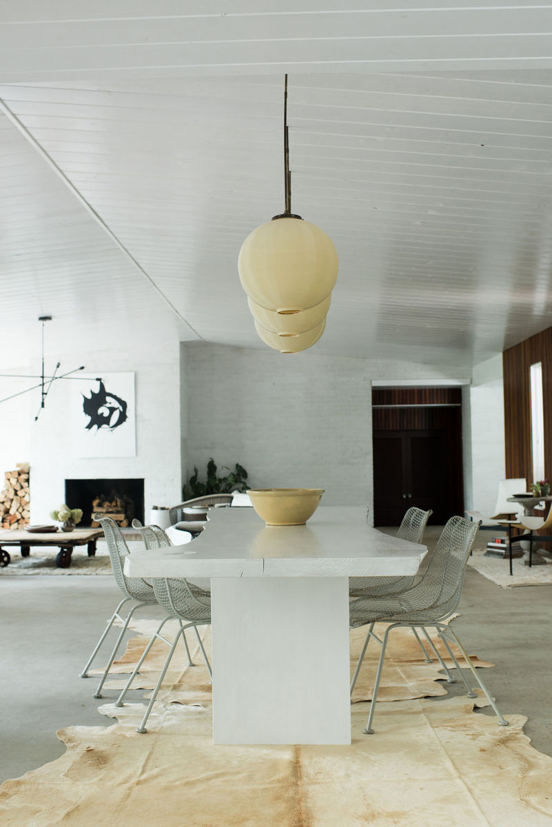 Beautiful home decor & interior design ideas! Dining area with Midcentury Modern design, hide rug, white live edge table, and wire chairs. #diningroom #interiordesign #midcenturymodern #leanneford #whitedecor #liveedge #rusticmodern