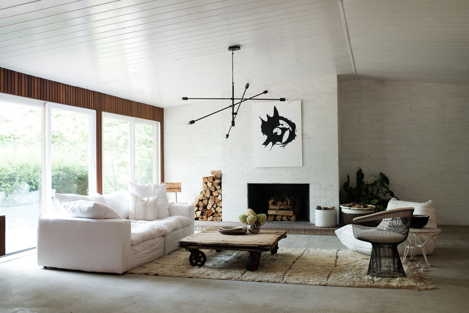 Interior design ideas & beautiful home decor ! A living room with Midcentury Modern design, white walls and furniture, and Sputnik chandelier. Design by Leanne Ford. #livingroom #interiordesign #midcenturymodern #leanneford #allwhite #whitedecor