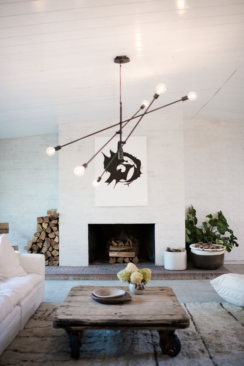 White living room with black accents, designed by Leanne Ford with Sputnik chandelier, rustic coffee table, white sofa, and white brick fireplace. #leanneford #livingroom #rusticdecor #sputnik