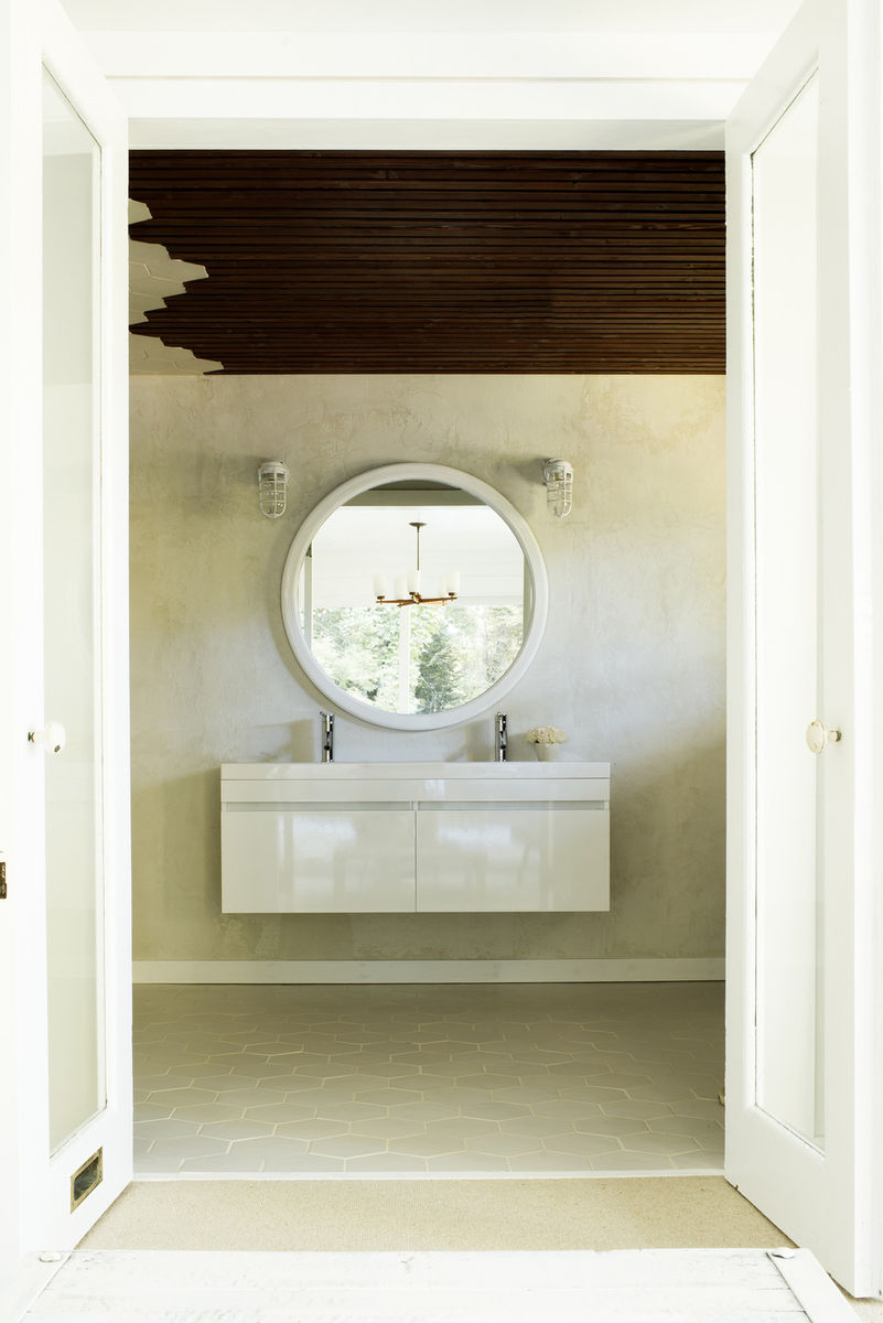 Leanne Ford designed bathroom with floating modern white lacquer vanity, round mirror, and nautical cage wall sconces. Tone on tone space with dark paneled wood ceiling. #leanneford #minimal #bathroom #vintagechic