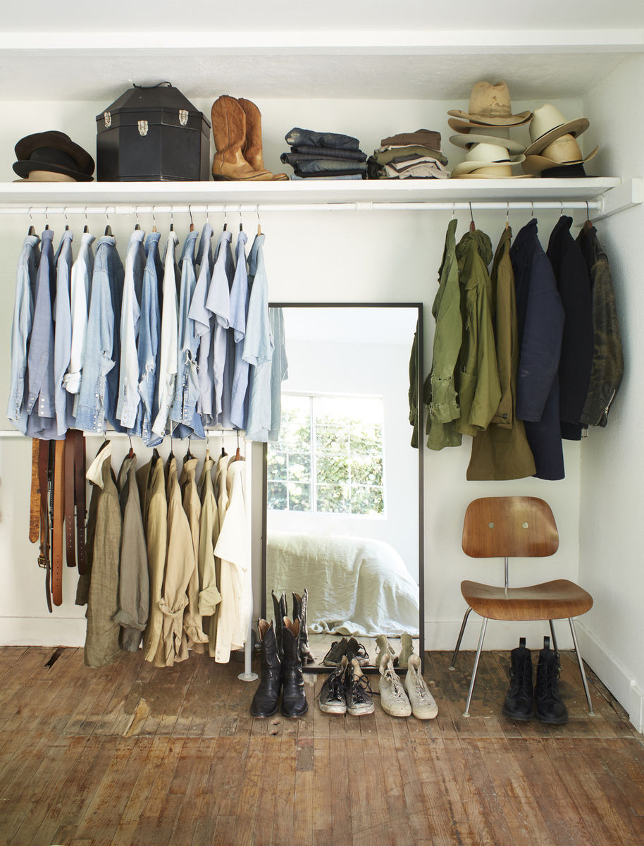 Minimal rustic closet designed by Leanne Ford with color coordinated hung clothing and accessories. #closet #leanneford #minimal #modern