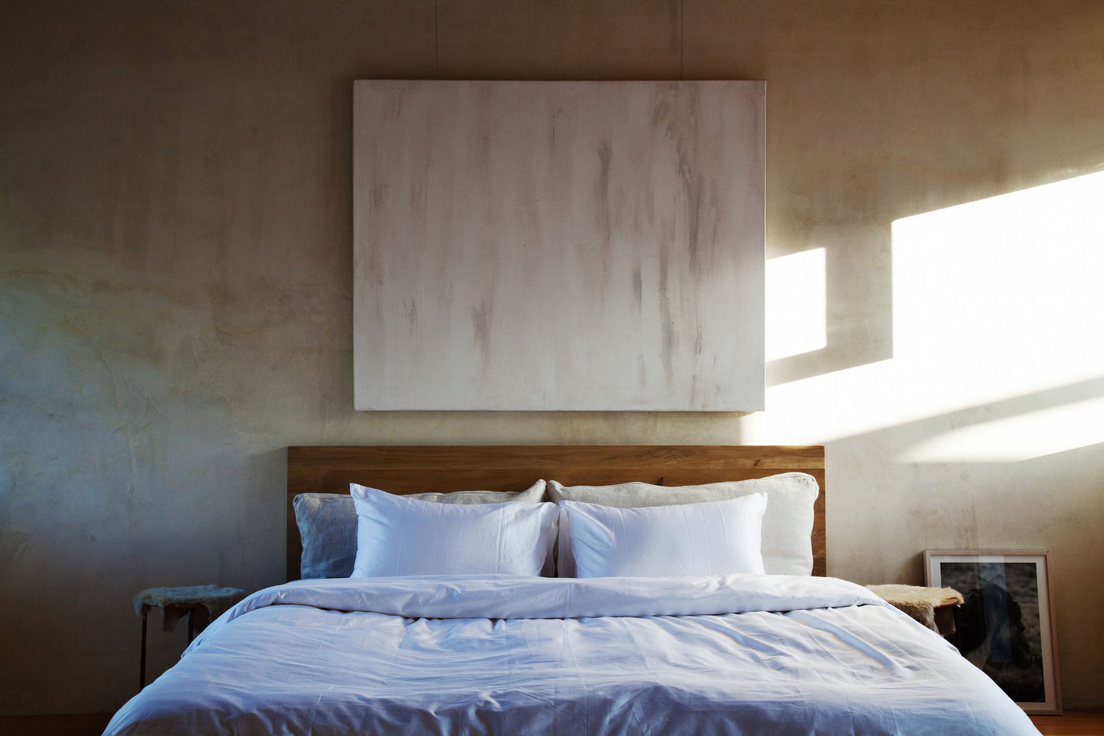 Minimal rustic chic bedroom designed by Leanne Ford with white linens, abstract painting, and tone on tone. #leanneford #bedroom #minimal #toneontone #modern