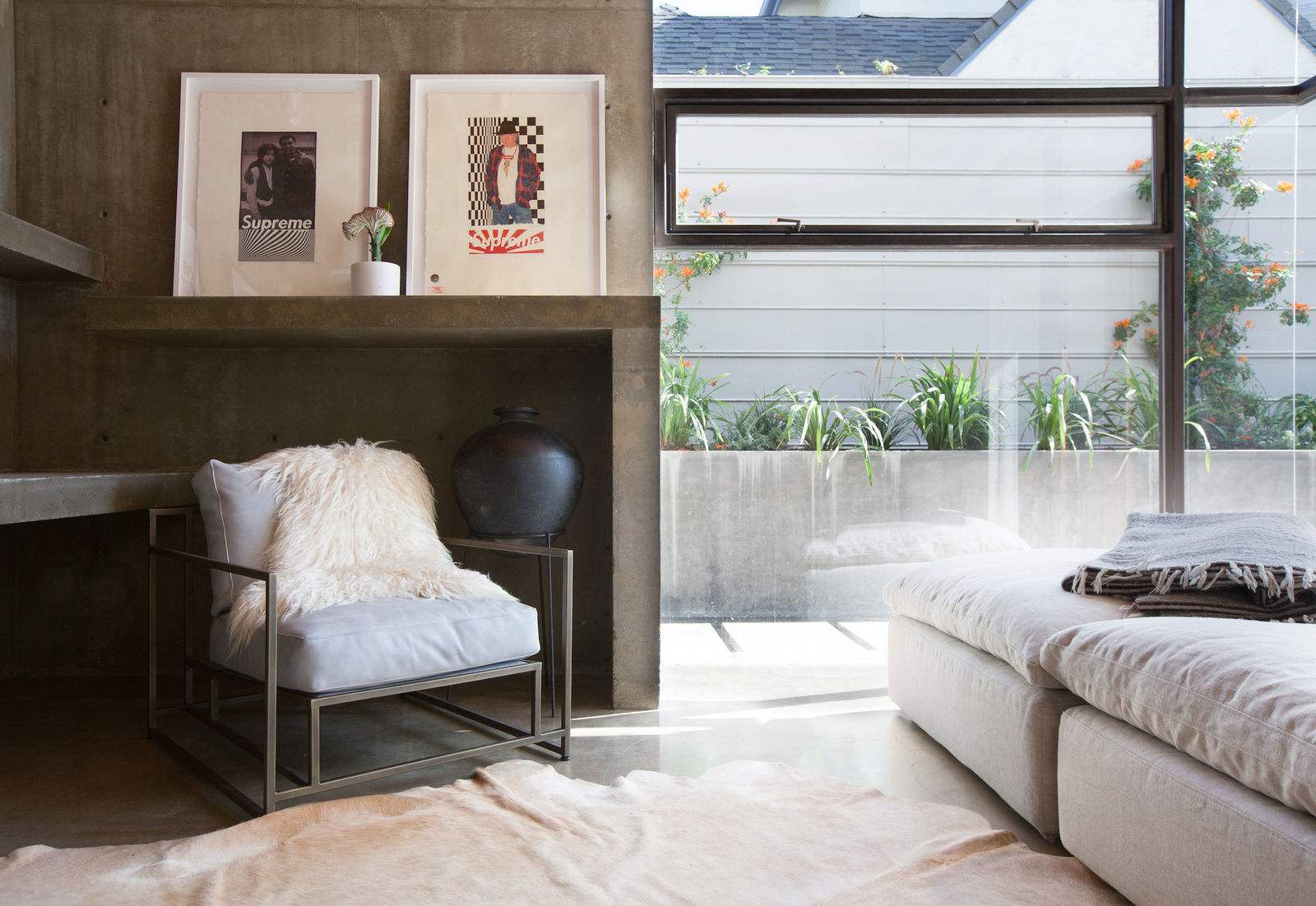 Organic and natural California chic styled interior by Leanne Ford with modern upholstered arm chair, cow hide rug, and huge wall of glass. #leanneford #rusticdecor #vintagechic