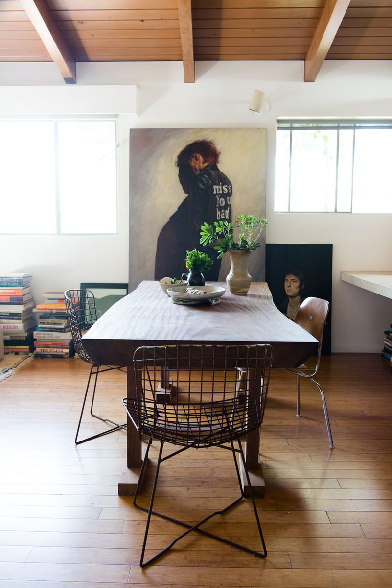 Undone and effortless chic dining room designed by Leanne Ford with live edge dining table, Bertoia wire chairs, and casually placed paintings and stacks of design books on wood floor. #leanneford #midcenturymodern #bertoia #liveedge