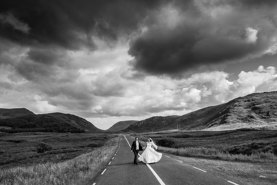 couple walking on the road in a black and white image