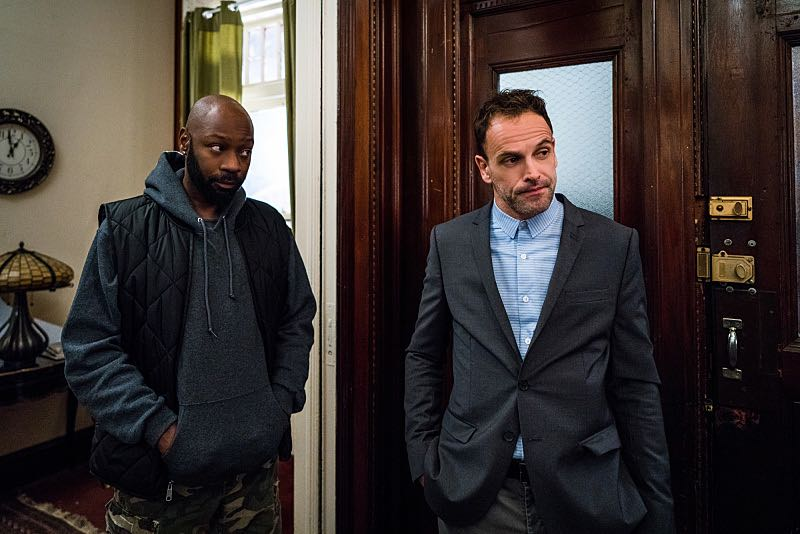 """""""It Serves You Right to Suffer"""" -- When Shinwell comes to Holmes and Watson for help after he's framed for a gang killing, they have three days to find the real murderer before he is arrested and sent back to jail, on ELEMENTARY, Sunday, Dec. 11 (10:00-11:00 PM, ET/PT) on the CBS Television Network. The episode was directed by series star Aidan Quinn, in his television directorial debut. Pictured (L-R) Nelsan Ellis as Shinwell Johnson and Jonny Lee Miller as Sherlock Holmes Photo: Michael Parmelee/CBS ©2016 CBS Broadcasting, Inc. All Rights Reserved"""