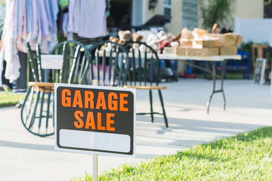 Garage sale sign in front yard of a house