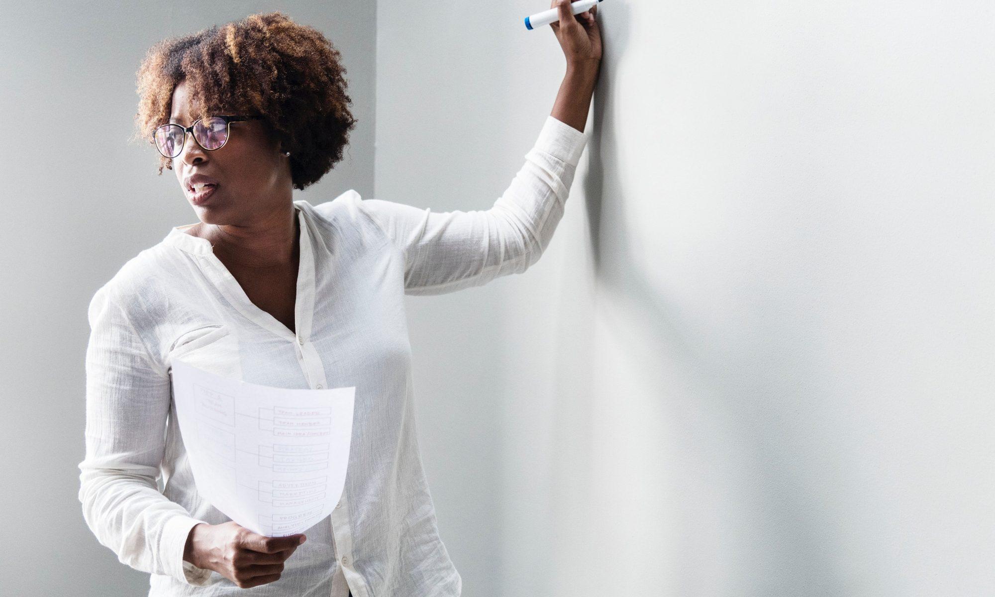 professora escrevendo em quadra branco