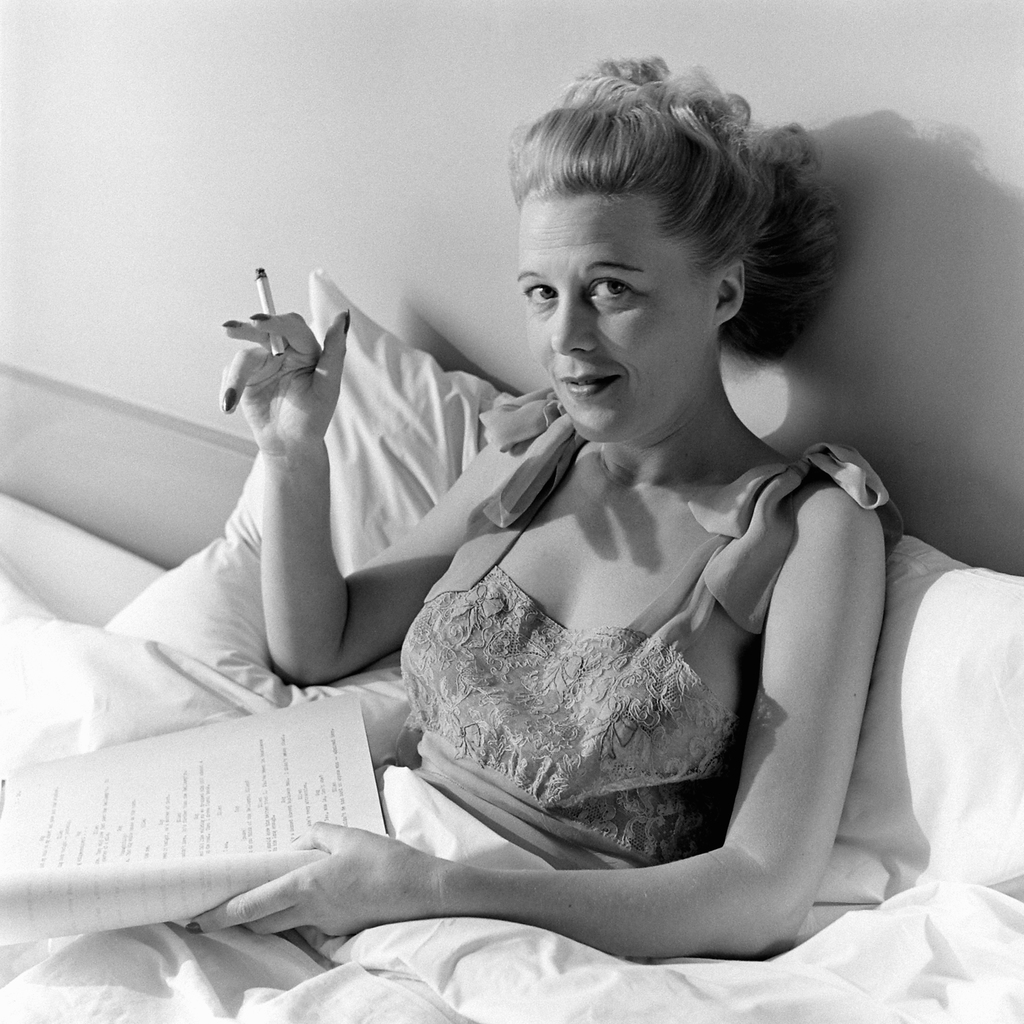 Joan Harrison, screenwriter and producer smoking and reading a script in bed at her home in Los Angeles, 1945