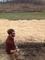 Jason spreading straw on garlic field.