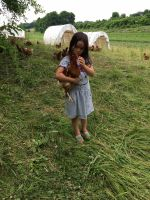 Farmer Mike's daughter Sage with one of our hens