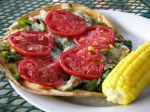 Homemade pizza with fresh veggies and side of sweet corn