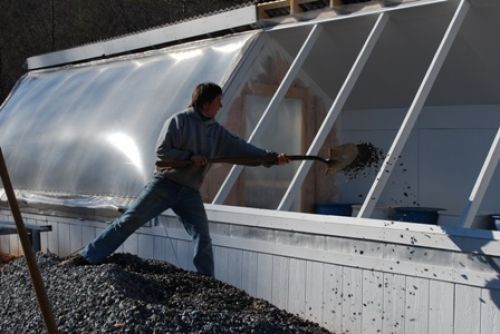 Shoveling gravel into the greenhouse addition
