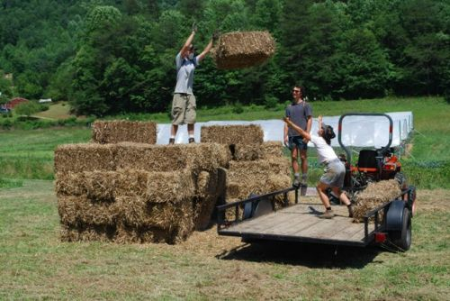 Cory tossing a straw bale to Brooke