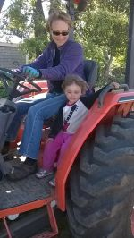 Amelia gets a tractor ride with Miss Barbara
