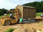Delivering and very carefully placing the well pump house.