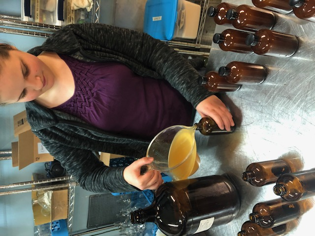 Madisyn bottling Supertonic in the new shop