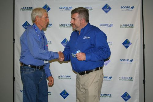 Rod receiving SCORE check - Hidden Pond Farm won America's Small Business Champions award