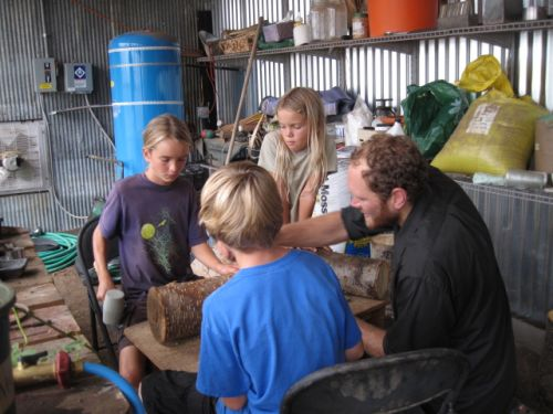 Tim and the children putting mushroom plugs in a log