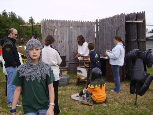School children try on armour while the Armourer works at the forge