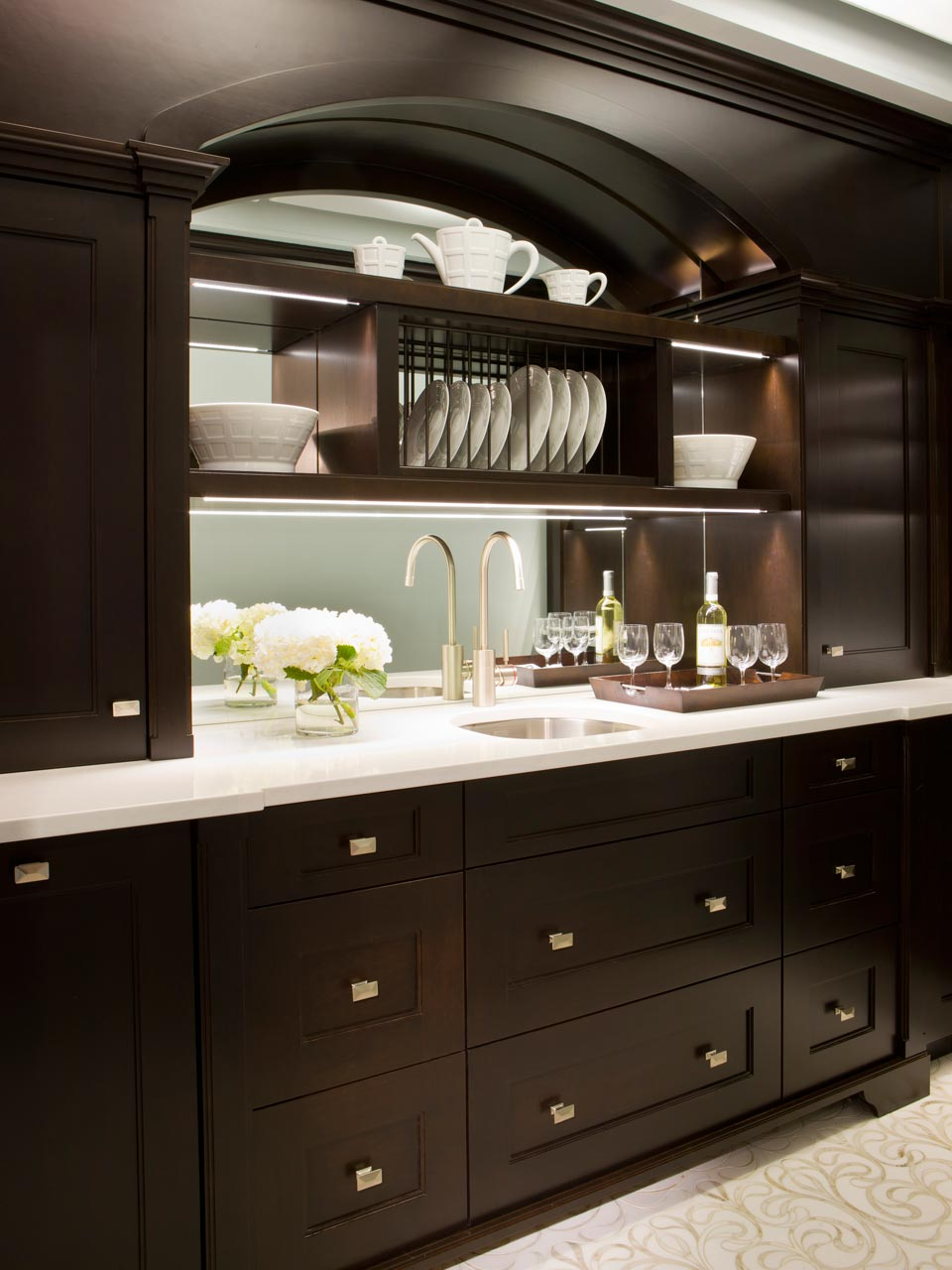 Elegant NYC butler's pantry features fully custom shaker style, frameless Rutt Handcrafted Cabinetry in walnut with a dark stain, mirror backsplash, white quartz countertop, and undermount sink with satin finish stainless faucet. Cabinetry features some open shelving to display dishes. Design by Tom Vecchio of Bilotta Kitchens.