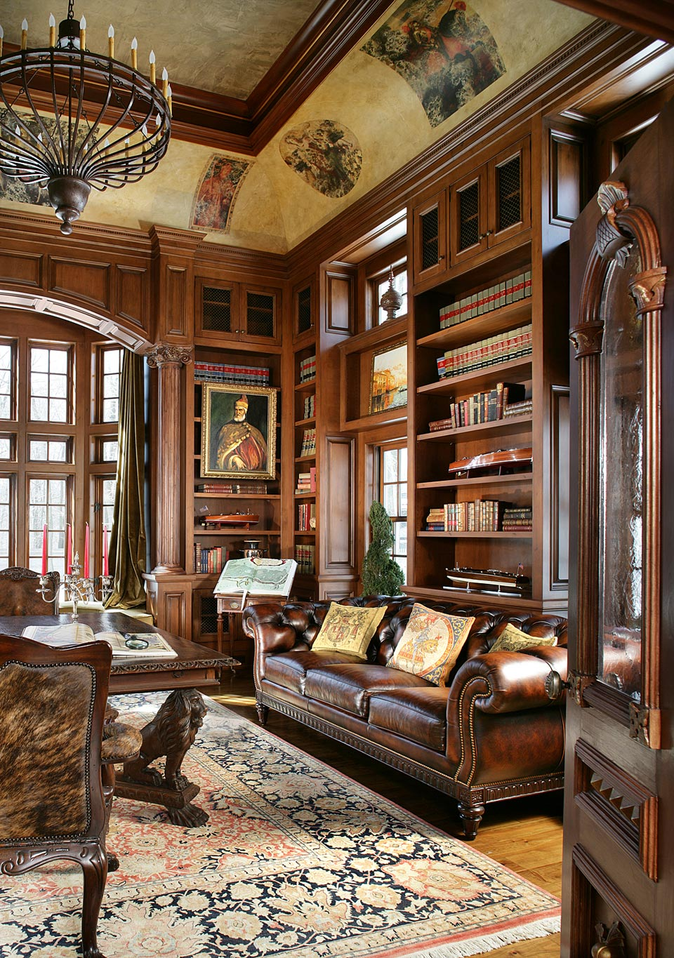 Ornate library features tray ceiling with mahogany molding and hand painted designs, large oil-rubbed bronze chandelier, mahogany archway over the floor-to-ceiling windows and custom mahogany shelving by Bilotta. Design by Regina Bilotta of Bilotta Kitchens.